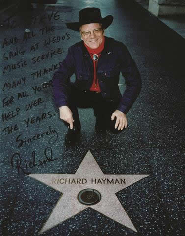 """BRIGHT STAR: Richard Hayman died on Feb. 5 at the age of 93 after being a Local 802 member since 1953. At left, Mr. Hayman visits the Hollywood Walk of Fame, where he was awarded his own star in 1960. The inscription on the photograph is to Local 802's Steve Danenberg, and it reads: """"To Steve and all the gang at Wedo's Music Service. Many thanks for all your help over the years. Sincerely, Richard."""" Allegro printed a formal obituary for Mr. Hayman in the March issue."""