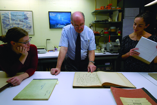 "Melissa Robason, Robert Sutherland and Sarah Vonsattel study a historic violin part of Wagner's ""Rienzi."""