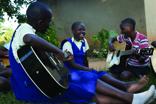 SMILES AND STRUMMING: Ugandan children experience the joy of playing music.