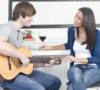 couple playing music guitar kitchen xavierarnau istock