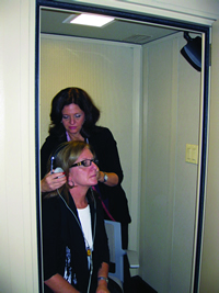 A special soundproof room helps audiologists test the hearing of musicians and other patients. Above, the audiologist is adjusting the headphones prior to the hearing test.