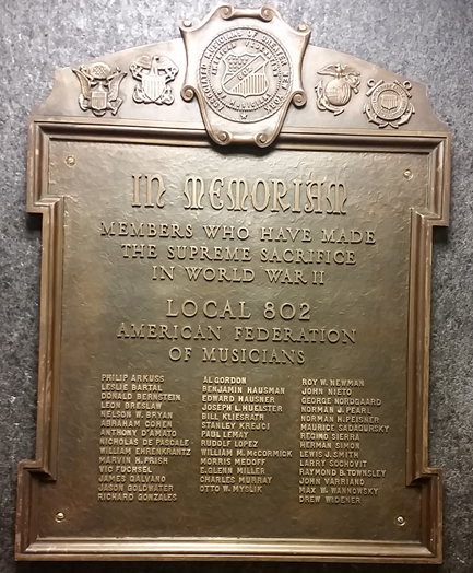 WE REMEMBER: This historic bronze plaque recognizes our members who gave their lives in World War II. As we reported previously in these pages, the plaque was lost when Local 802 moved from its previous site at Roseland to our current building. The plaque was eventually salvaged from a junkyard in Florida. Local 802 attorney Harvey Mars arranged (and paid) for its eventual return home. Please come and view the plaque in our lobby, just before you enter the club room.